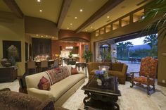 Indoor outdoor living room in tropically located home.  The living room is part of an open concept living space with mini-bar and large open...