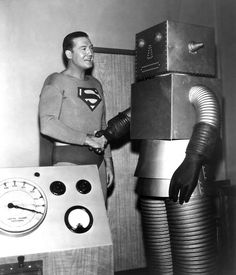 George Reeves as TV's Superman shakes hands with a robot