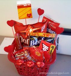 The red basket is from the Dollar Store, as are the hearts on the sticks and chocolate lips.  Inside you will find:  Hot Sauce  Big Red Gum  Red Hots  Hot Tamales  Spicy Beef Jerky  Doritos  Twizzlers  Cherry Chapstick  Cinnamon Bears   I think this is a perfect gift for a guy while still being cutesy enough to be fun and special.