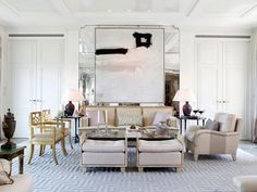 elegant white on white traditional living room with a greek key rug and tufted ottomans