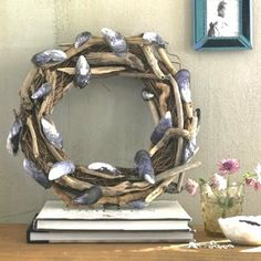 grapevine wreath with driftwood & mussel shells. This site has MANY shell wreaths! Will be making shell wreaths at our family beach week next month!!
