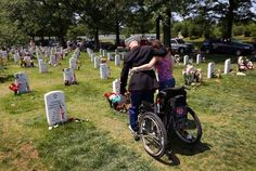 U.S. Marine Cpl. Miroslav Kazimir stands up with the help of his wife Marcela while visiting a grave at the National Cemetery on Memorial Day on May 28, 2012 in Arlington, Virginia. He had come to visit the grave of Marine Sgt. Sean Callahan who died in an IED attack in Afghanistan in April, 2011, the same attack that severely damaged both of Zazimir's legs. He is currently undergoing long-term therapy at the military hospital in Bethesda, MD.