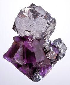 Galena cube perched atop reddish-purple fluorite and smaller galenas. Source: Denton Mine, Hardin County, Illinois, United States of America.