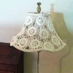 I took an old lamp shade and covered it with two doilies and stitched them onto the frame.