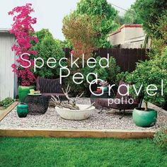 Loose gravel in shades of gray, white, and tan gives this raised patio a beachy feel to complement the relaxed look of the low-slung wood-sided cottage it sits behind.