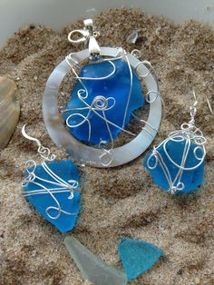 Wire wrapped aqua cultured sea glass shell framed  pendant with matching wire wrapped earrings. Just one of the creations at Sandy's Seashell Shop in The Prayer Box.