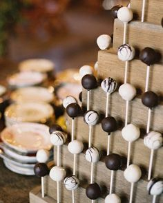 Cake pops in three flavors displayed on a tiered stand made to mimic a traditional cake