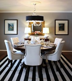 black round table, upholstered chairs, striped rug, nickel and black pendant light...