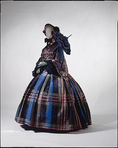 Plaid silk, pleated; European, ca 1857. This view shown with black lace collar, undersleeves; colored gloves, decorated bonnet, parasol. MET