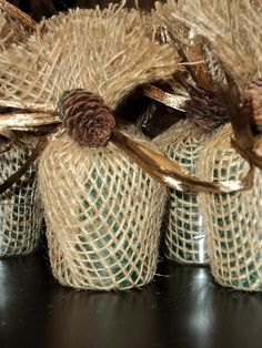 Candles wrapped in burlap with a pine cone embellishment given out as a favor