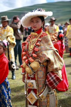 Litang Horse Festival, 2008 or earlier | Beautiful woman from the Litang area in traditional clothing. She wears a chuba and sheepskin hat, multiple huge and heavy prayer boxes and linking chains popular in Kham, and  a spectacular necklace with enormous pieces of coral, this alone is probably worth tens of thousands of dollars/euros. The Litang Festival (banned since 2008 for political reasons) in eastern Tibet is one of the best places to experience traditional Tibetan culture.