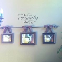 Picture frames hung from ribbon on a curtain rod