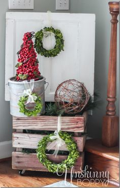 Pretty rustic Christmas vignette with boxwood wreaths and a cranberry topiary in a minnow bucket.