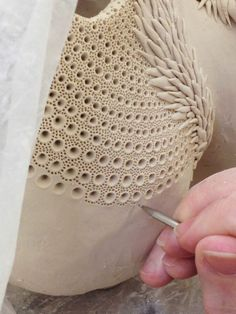 This is clay but I could turn a piece from wood then use a drill bit or countersinking bit to make similar holes and then use a smaller bit to make the other holes or use a wood burner to burn marks.