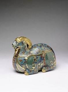 Box in the form of a ram, cloisonne enamel on copper, the plain parts gilt.  The upper part of the body forms the lid. The designs include the markings of the tail (dark blue), sides (green scales) and belly (lilac and yellow scales); the remaining enamelled surfaces displaying floral scrolls on a turquoise blue ground.  Shaped wood stand with carved and pierced ornament. Beijing, China (made) 1736-1795