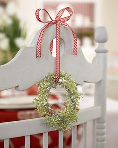 a tiny wreath hung from the back of a chair with gingham ribbon