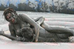 Two girls sumo wrestling in the mud at the Boryeong Mud Festival