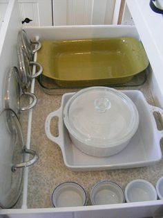 Use a tension rod to secure pot lids along the side of a drawer or cabinet