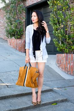 Blogger The Fancy Pants Report layers her Gap cardigan over shorts for a sophisticated summer look.
