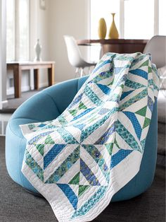 This calming quilt features strip-pieced triangle units in springy blue, green and white fabrics that are arranged as four sides of a square block. Digital pattern available! #Quilty
