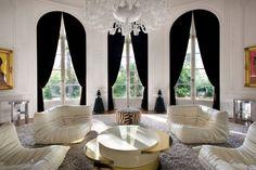 Lenny Kravitz Paris apt living room white glam fur chandelier 1970s brass table Mohammed Ali Warhol zebra