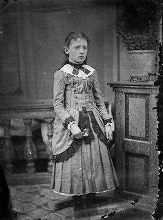 An 1800's, beautifully-attired, post-mortem (posting stand visible behind her) Victorian girl holding flowers.