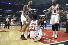 Bulls forward Jimmy Butler is helped up off the floor by teammates Malcolm Thomas and Carlos Boozer.