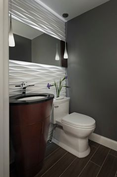 Powder room with a gorgeous accent wall. An excellent installation idea for our Satin Bianco Wave!