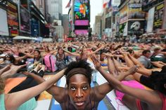 Reaching for the Sun, Photograph by Mario Tama, Getty Images 1000+ people practicing yoga in Times Square to celebrate the Summer Solstice