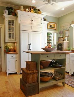 Cottage Style Kitchen...love the green island table and the stack of baskets.