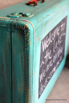 painted chalkboard suitcase - could turn it into an opening shelf mounted on the fence. maybe put a painted frame around it.