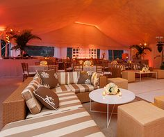 Wicker furniture and coral motif pillows along with orange uplighting create a beachy ambience.