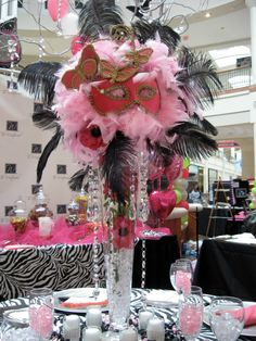 Want something a little out of the ordinary? Woo your guests with this amazing masquerade themed centerpiece!! Adorned with black feathers, butterflies, and hanging crystals!