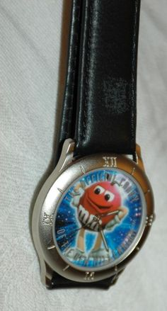 M&M Millennium Wrist Watch. New & Unused. Dated 1998. Still has the protective cover over they crystal.  The band is black leather that is embossed with the M&M logo .  The condition is excellent....