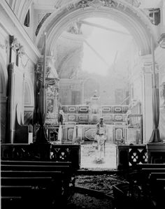 """""""Pvt. Paul Oglesby, 30th Infantry, standing in reverence before an altar in a damaged Catholic Church. Note: pews at left appear undamaged, while bomb-shattered roof is strewn about the sanctuary. Acerno, Italy."""" Benson, September 23, 1943. 111-SC-188691."""