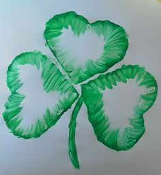 Using heart cookie cutters dipped in green paint to make shamrocks