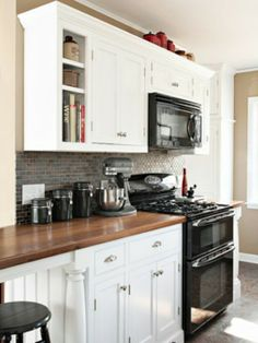 Black appliances in hard contrast against white cabinets and butcher block countertops.