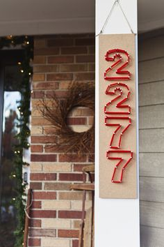 Easy instructions for creating house numbers using nails and yarn -- adds a fun pop of color to your front door! #holiday #DIY #curbappeal #christmas | From The Home Depot's Apron blog series Holiday Style Challenge and Michelle of 4 Men 1 Lady