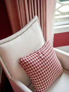 The modern styling of classic, upholstered armchairs with nailhead detail bring elegance into the space. A repeated theme of white and red is creatively translated into houndstooth accent pillows -->  http://hg.tv/v81t