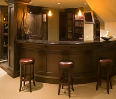Be sure to read why we like this home's corner basement bar. Clever layout wraps around columns and stairwell.