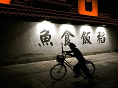 """Cyclist, China    Photo: Dominic Rubin.   Walking along one of the many canals in the ancient city of Suzhou, a stall worker mounts her bike for her commute home, creating a pleasing silhouette set against bold Chinese writing and illuminations on a centuries-old dwelling. Suzhou, Jiangsu Province, China."" - We once visited Suzhou on a cold day. We were all shivering  but my dad had the warmest smile. (sigh) I really miss my dad."