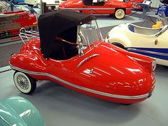 "1958 Brutsch Rollera. Egon Brütsch built Four Cars for Display at the 1956 IFMA.  Had a larger bench seat and a 100cc motor.  In the summer of 1957, after attempting to generate interest at the IFMA, Brütsch loaded 2 ""normal sized cars"" with 3 Mopettas and a Rollera on the Roof and in the Trunk and drove around with his Secretary looking for someone who might be interested in producing them.  Only 8 units were ever produced (licensed in France) and only Four are known to survive today."