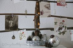 rustic card display Christmas tree.  I like the touch of the random eclectic ornaments hanging from the branches and the beautiful display at the bottom. From: http://www.songbirdblog.com/2012/12/christmas-card-display-tree/#