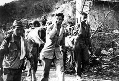 Captured Japanese photograph of Americans POWs carrying the sick and the wounded during the Bataan Death March, Philippine Islands, Apr 1942...