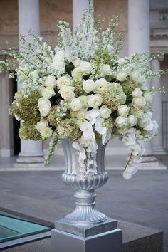 A sculptural, statement floral arrangement of clean white roses and orchids. McCalls Catering and Events.