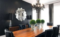 black imperial trellis wallpaper, nailhead dining chairs, mirrored sunburst mirror, and a black crystal chandelier.