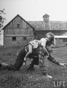 Farmer's daughter Sandra Edson riding on the back of Land Corps volunteer Murray Blackman, Vermont, United States, 1942, photograph by Alfred Eisenstaedt.