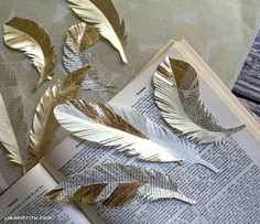 Gold Paper Feathers (gift toppers) at lia Griffith blog http://liagriffith.com/diy-paper-feathers-in-gold/ door decs, diy ideas, book art, diy paper feathers, gift packaging, feather tree, book pages, blog, paper feather diy