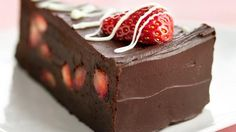 Indulge in a decadent chocolate cake dessert bursting with fresh strawberries and enrobed in rich ganache.