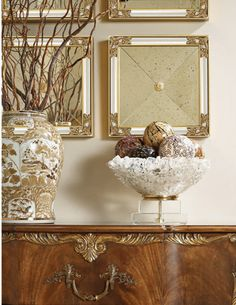 Set of four mirrors with antiqued mirror glass from La Barge are shown with a Maitland-Smith chest and accessories